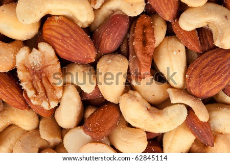 Mixed nuts including almonds, cashews, hazelnuts and walnuts sprinkled with salt. - stock photo