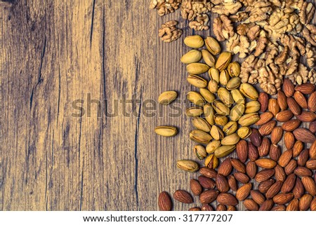 Mixed nuts on wooden background - Nuts frame top view. Toned - stock photo
