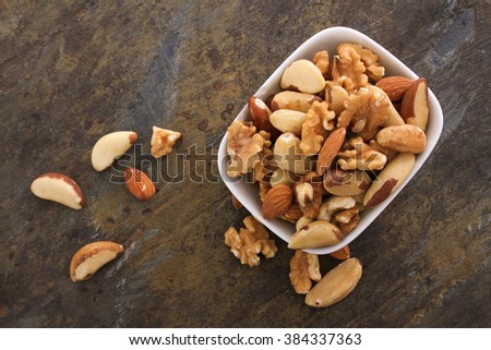 mixed nuts snack selection in white dish - stock photo