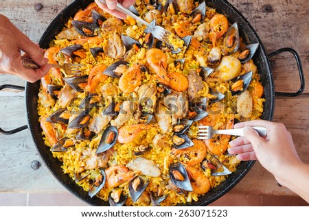 Mixed paella and hands with forks taking rice. Aerial view. - stock photo