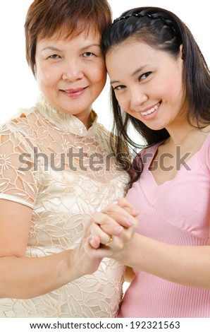 Mixed race beautiful Asian family portrait. Elderly mother and adult daughter holding hands bonding isolated on white background. - stock photo