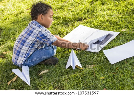 Mixed Race Boy Learning How to Fold Paper Airplanes Outdoors on the Grass. - stock photo