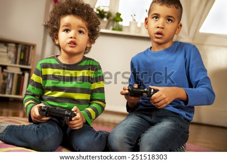 Mixed race boys playing video games at home. - stock photo