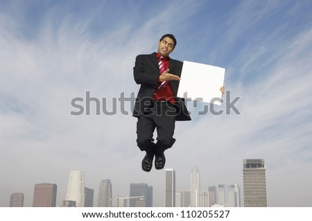 Mixed race businessman in midair showing a blank placard - stock photo