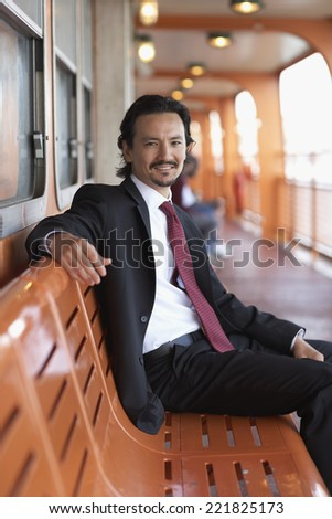 Mixed race businessman smiling on bench - stock photo