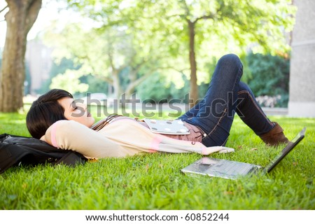 Mixed race college student sleeping on the grass at campus - stock photo