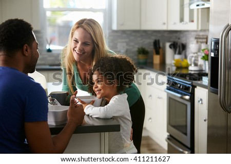 Mixed race couple and daughter talk together in the kitchen - stock photo