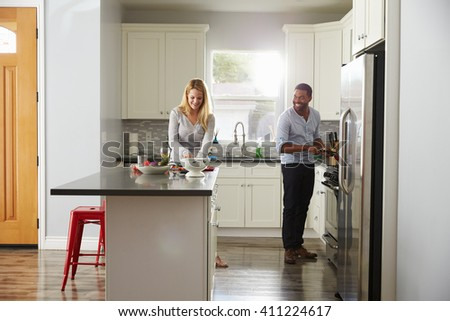 Mixed race couple preparing a meal in their kitchen - stock photo