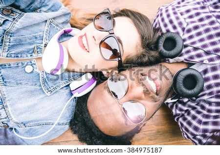 Mixed race couple taking self portrait lying down on the floor - stock photo