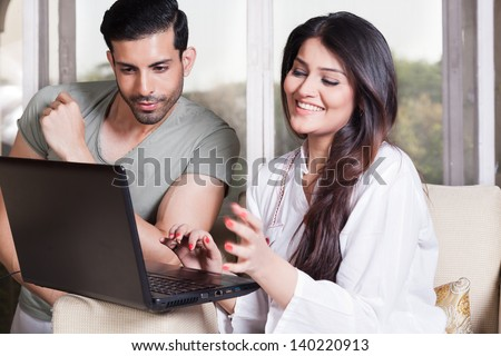 mixed race couple using the laptop sitting on a white sofa. - stock photo