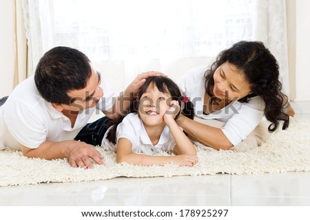 mixed race family lying on the floor  - stock photo