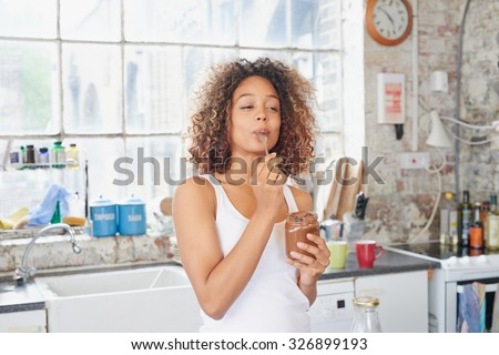 Mixed race girl indulging cheeky face eating chocolate spread from  jar using spoon savoring every  mouthful - stock photo
