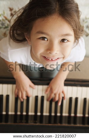 Mixed race girl playing piano - stock photo