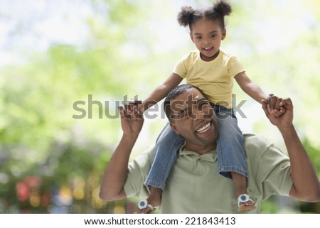 Mixed Race girl sitting on father's shoulders - stock photo
