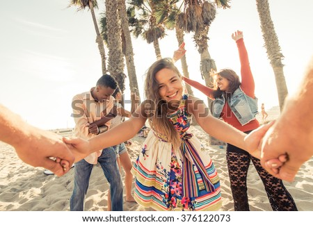 Mixed race group of friends having fun outdoor in Santa monica beach. Students celebrating and making party outdoor - stock photo