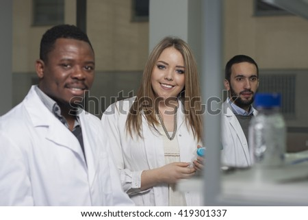 Mixed-race group of young workers are working in biochemistry lab, portraits of lab technicians - stock photo