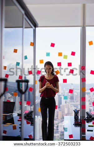 Mixed race secretary working in modern office in skyscraper, writing and sticking adhesive notes with tasks on window.  - stock photo