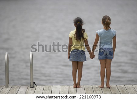 Mixed Race sisters holding hands - stock photo