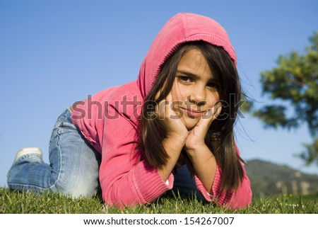 Mixed race smiling girl lying on the meadow - stock photo