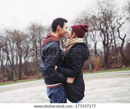 Mixed race teenage couple about to have a passionate kiss in park. Handsome young man and beautiful young woman in warm clothes together. - stock photo