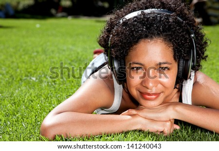 Mixed race woman happily listening to music on headphones - stock photo