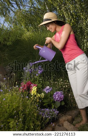 Mixed Race woman watering flowers - stock photo