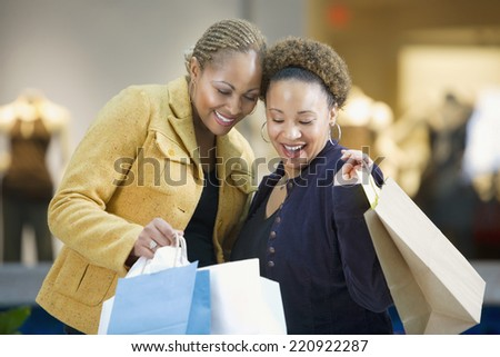 Mixed Race women with shopping bags - stock photo