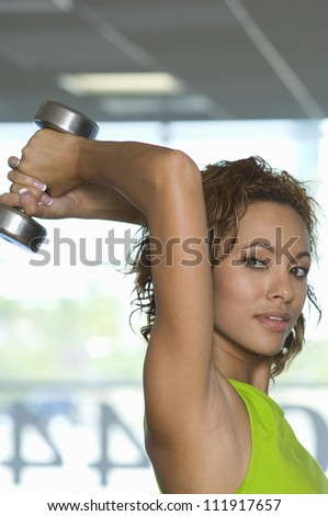 Mixed race young woman lifting weights at a gym - stock photo