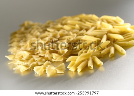 Mixed raw uncooked fusilli macaroni conchiglie penne farfalle pasta types displayed on brushed steel surface - stock photo