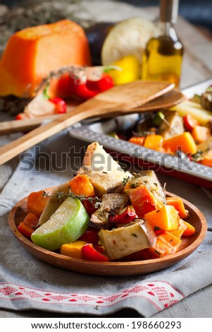 Mixed roasted vegetables with thyme in a tray and wooden plate. Selective focus. - stock photo
