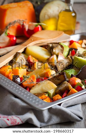 Mixed roasted vegetables with thyme in a tray. Selective focus. - stock photo