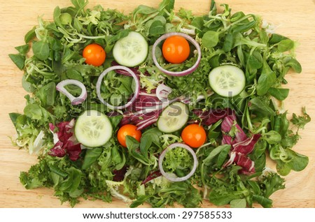 Mixed salad on a wooden board viewed from above - stock photo