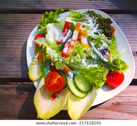 Mixed salad with endive, tomatoes,peppers,chicory topped by yoghurt dressing on a rustic wooden bench. Instagram-like retro filter added.  - stock photo