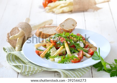 Mixed salad with fried white asparagus, feta cheese, rocket and cherry tomatoes, served with baguette - stock photo