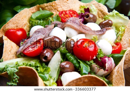 mixed salad with mozzarella and anchovy in a bread basket - stock photo