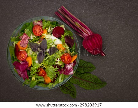 Mixed salad with salad ingredients on the dark background - stock photo