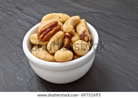 Mixed Salted Nuts in bowl on dark grey slate background. - stock photo