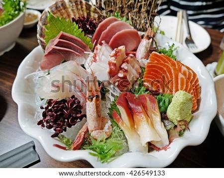 Mixed Sashimi set with Salmon, shrimp,Sea urchin,Tuna on white plate (Japanese food). Delicious Japanese sashimi sushi set or platter. Raw fresh Salmon meat sashimi and Raw fresh Tuna meat sashimi.  - stock photo