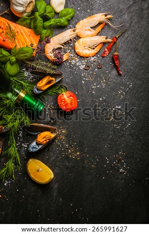 Mixed seafood being prepared in a kitchen with salmon steaks, pink prawns and mussels with fresh herbs and spices on a slate counter, view from above with copyspace - stock photo