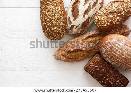 Mixed whole grain health breads on rustic white painted wood. - stock photo