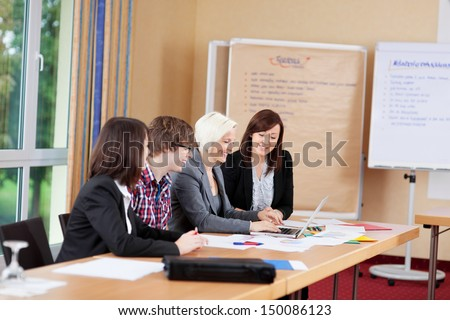 mixed working group looking at laptop - stock photo