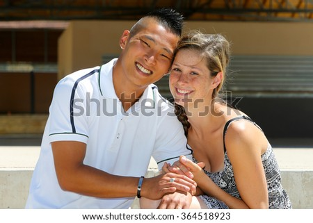 Mixed young couple in a park - stock photo