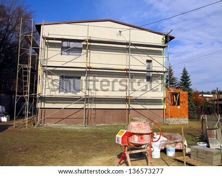 mixer for mortar and concrete and scaffolding repaired the walls of the building, insulation and renovation of the facade - stock photo