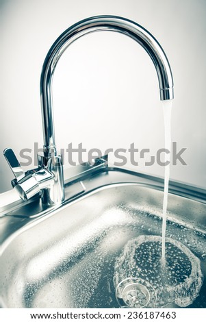 mixer tap with flowing water, light background - stock photo