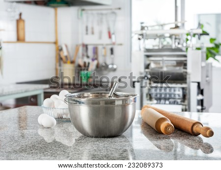 Mixing bowl with eggs and rolling pin on countertop in commercial kitchen - stock photo