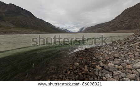 Mixing rain water and melting water rivers flowing through arctic tundra, Greenland - stock photo