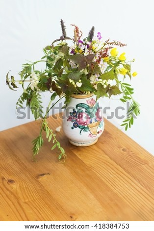 Mixture of blooming meadow wildflowers in vase with flower decoration on wooden table on white background, still life - stock photo
