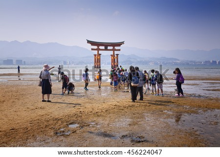 MIYAJIMA, JAPAN - MAY 27: Tourists walk around the famous floating torii gate of the Itsukushima Shrine on Miyajima at sunset on May 27,2016 in Miyajima, Japan - stock photo