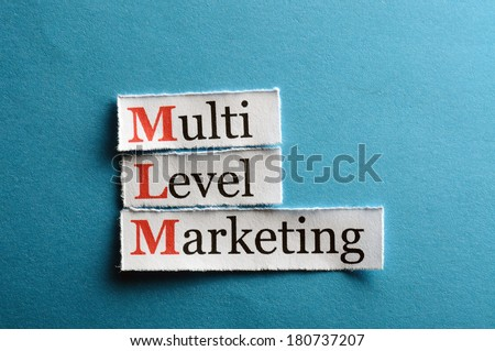 mlm - multi level marketing on blue paper - stock photo
