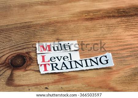 MLT- Multi Level Training written on paper on wooden background - stock photo